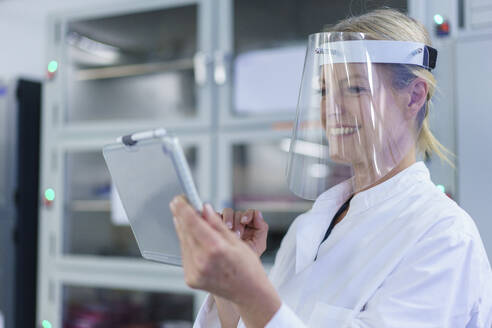 Smiling mature female scientist wearing protective face shield while using digital tablet at laboratory - MOEF03401