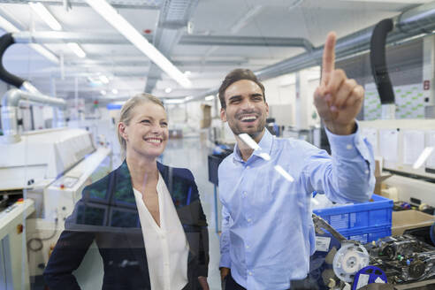 Happy young male technician pointing at graphical interface on glass in factory - MOEF03410