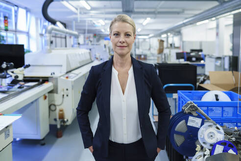 Confident smiling businesswoman standing with hands in pockets in illuminated factory - MOEF03413