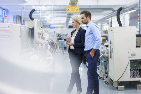 Mature businesswoman holding digital tablet while standing with young colleague at illuminated factory - MOEF03422