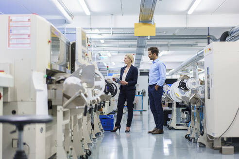 Male technician standing near businesswoman analyzing machinery at factory - MOEF03428