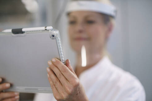 Close-up of female scientist wearing protective face shield while using digital tablet at laboratory - MOEF03461
