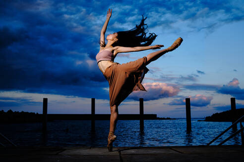 Side view of graceful ballerina in pointe shoes dancing on pier near lake while balancing on leg on background of amazing sunset in evening - ADSF15712