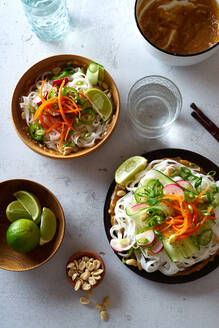 Healthy lunch with vegan rice noodle salad made with fresh vegetables, lime and peanut sauce and a glass of water - ADSF15778