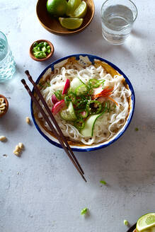 Top view of vegan rice noodle salad made with fresh vegetables, lime and peanut sauce - ADSF15790