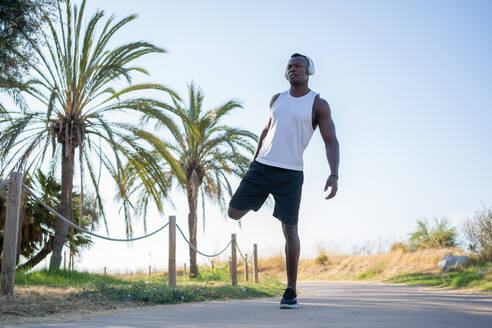 Full body of young muscular African American sportsman in headphones and sunglasses doing stretching exercise while preparing for jogging in city park in summer day - ADSF15814
