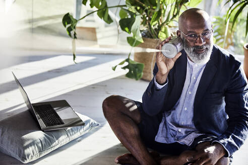 Man listening from tin can phone while sitting at home - FMKF06372