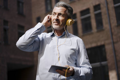 Businessman with headphones using phone while standing against building - JOSEF02020