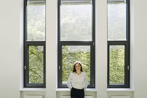 Businesswoman with hands behind back standing against window at office - JOSEF02131