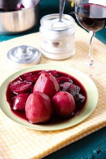 From above of tasty red wine poached pears in plate placed on table in restaurant - ADSF15862