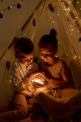 Brother and sister sitting in room while holding christmas light - GMLF00650