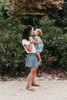 Mother and daughter kissing each other while standing in public park - EBBF00780