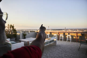 Cropped image of man pointing at clear sky from building terrace during sunset - FMKF06407