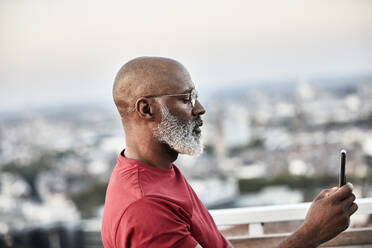 Mature bald man with white beard using smart phone for photographing sunset from rooftop - FMKF06446
