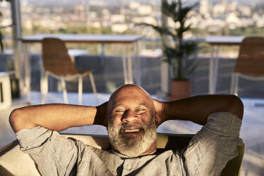 Smiling mature man relaxing on sofa at building terrace during sunset - FMKF06461