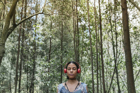 Young woman with eyes closed listening music through headphones against trees at park - DSIF00157