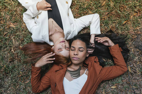 Young multi-ethnic female friends with eyes closed lying on grass at park - DSIF00160