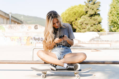 Blond woman using smart phone while sitting with skateboard at park on sunny day - FMOF01178