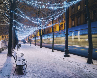 Blurred motion of tram by snow covered footpath in illuminated city during Christmas - LCUF00112