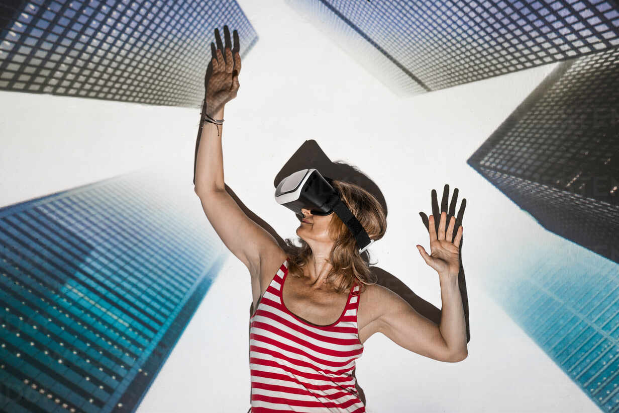 Unrecognizable Female In Casual Wear And Vr Headset Standing With Arms Raised Against Contemporary Skyscrapers Inside