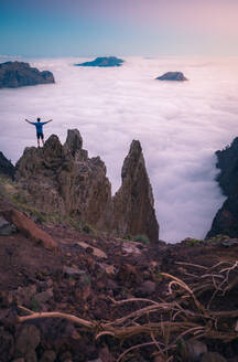 Back view of anonymous male traveler standing with outstretched arms on rocky hill in highlands and enjoying amazing view of clouds - ADSF15916