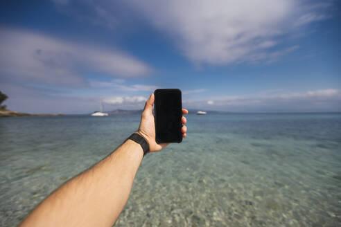 Hand of male tourist holding smart phone against sea at Praia de Figueiras, Cíes Islands, Vigo, Pontevedra Province, Galicia, Spain - RSGF00290