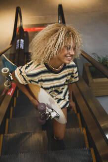 Smiling blond Hispanic woman holding skateboard while standing on escalator - MRRF00542