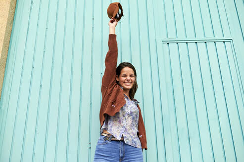 Happy woman with hand raised holding cap up while standing against blue metal door - KIJF03295