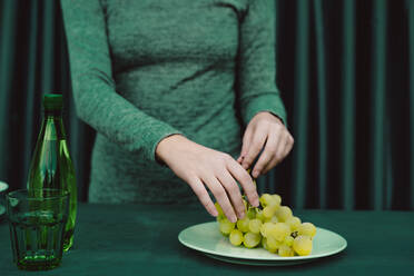 Midsection of woman with grapes, glass, bottle kept on table - ERRF04511