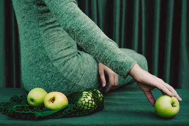 Midsection of woman with green apple touching while sitting on table against curtain - ERRF04514