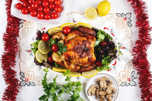 Top view of festive table served with baked chicken with various vegetables and placed near plates and fruits - ADSF16117