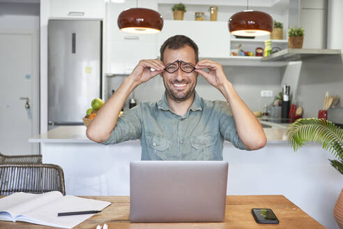 Playful male freelancer holding eyeglasses while sitting with laptop at home - VEGF02984
