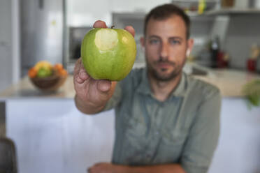 Man showing bitten apple while sitting at home - VEGF02987