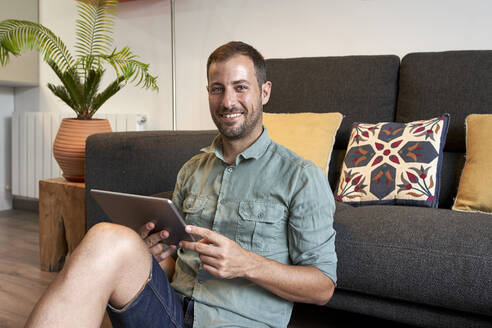 Smiling man sitting on floor with digital tablet against sofa in living room at home - VEGF02996