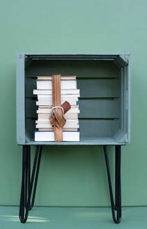 Books kept in green color crate with hairpin leg against turquoise colored background - GISF00662