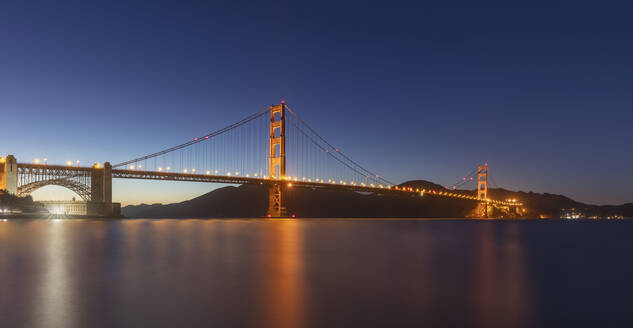Illuminated Golden Gate Bridge over sea against clear sky at San Francisco, California, USA - AHF00120