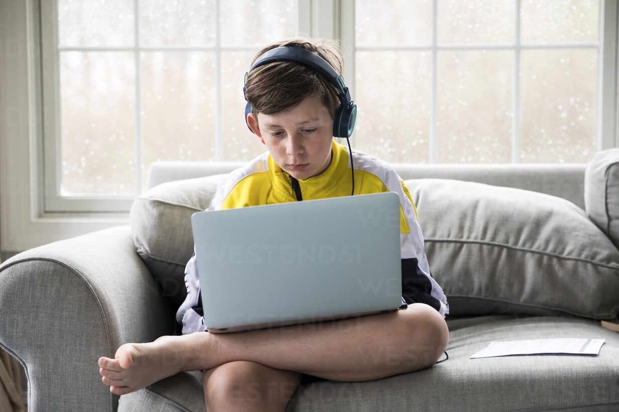 Tween Boy Using Laptop for Virtual School Sits on Living Room Couch - CAVF89735 - Cavan Images/Westend61