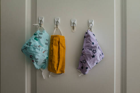 Three cloth masks hanging on hooks in closet - CAVF89753