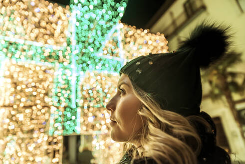 A young girl in a hat looking through Christmas lights - CAVF89762