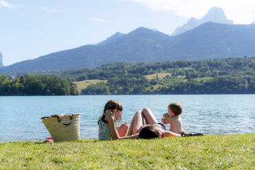 Mother and daughters relaxing while lying on grass by lake - GEMF04192