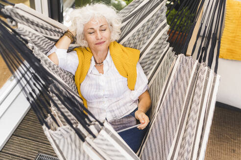 Mature woman with hands behind head holding digital tablet sitting on hammock at home - UUF21627