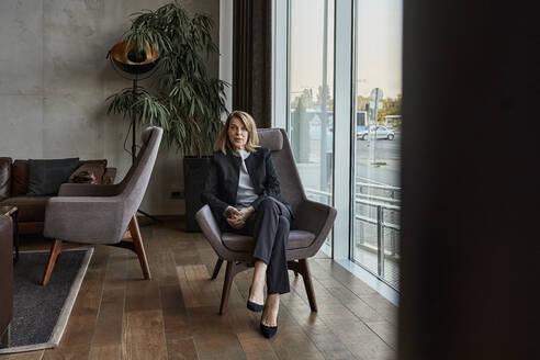 Serious senior woman sitting on chair in hotel lobby - ZEDF03859