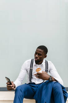 Male African professional using mobile phone while holding cup and sitting against window in city - EGAF00812