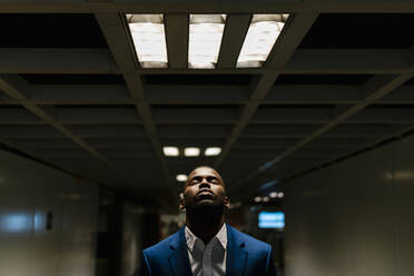 Male professional with eyes closed standing under illuminated light in subway - EGAF00821
