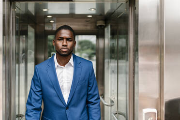 Confident young male professional walking in corridor - EGAF00827