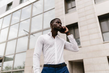 Male professional on the phone looking away while standing against office building in city - EGAF00836