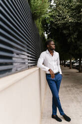 Young male entrepreneur looking away while leaning on surrounding wall in city - EGAF00839