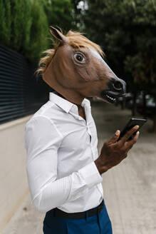 Male entrepreneur wearing horse mask while holding smart phone in city - EGAF00848