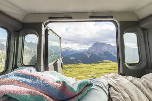 Male tourist relaxing in campervan against mountain range, Sesto Dolomites, Dolomites, Alto Adige, Italy - MMAF01399