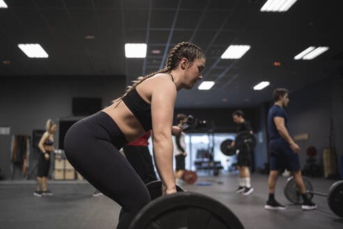 Woman picking barbell with people exercising in background at gym - SNF00557